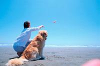 ビーチでフリスビーを投げる女性と犬