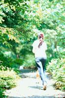 林の中を犬と走る女性の後姿 21014001174| 写真素材・ストックフォト・画像・イラスト素材|アマナイメージズ