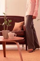 茶色のソファの横に立つ女性