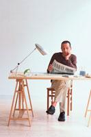 デスクで英字新聞を読む日本人男性