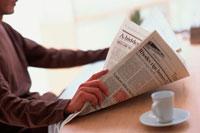 テーブルで英字新聞を読む男性