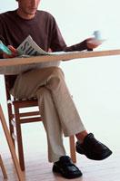 テーブルで新聞を読む男性