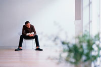 椅子に座って本を読む男性