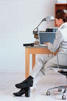 ノートパソコンに向かうスーツの女性