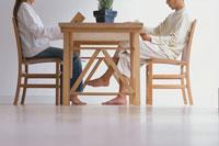 ダイニングテーブルで読書するカップル