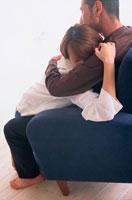 青いソファで抱き合うカップル