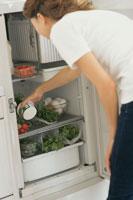 冷蔵庫から物を取り出す女性