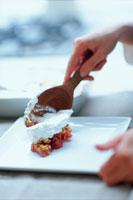 お皿のデザートにクリームをのせる手