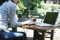 ガーデンテーブルで本を読む日本人女性