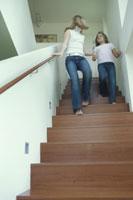 素足で階段を下る母と娘