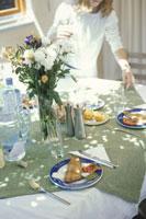 料理をテーブルセッティングする女性