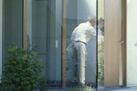 扉の中にいる新聞を持った外国人男性
