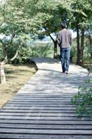 木道を裸足で歩く男性の後姿