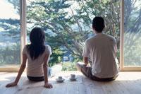 座って外を眺める男女の後姿