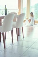 ダイニングルームの窓辺に座った女性 21022001750| 写真素材・ストックフォト・画像・イラスト素材|アマナイメージズ
