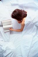 ベットで寝そべって読書する女性