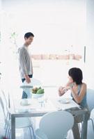 コーヒーを飲む女性と立っている男性