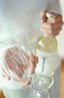 女性が持ったワイングラスと白ワインボトル 21022001804| 写真素材・ストックフォト・画像・イラスト素材|アマナイメージズ