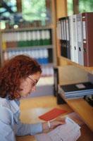 デスクで書類を見る女性 21022001848| 写真素材・ストックフォト・画像・イラスト素材|アマナイメージズ
