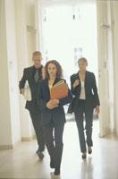 廊下を歩くスーツ姿の外国人男女