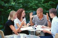 屋外のテーブルで話し合う外国人