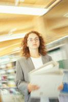 オフィスでファイルを持って歩く女性 21022001870| 写真素材・ストックフォト・画像・イラスト素材|アマナイメージズ