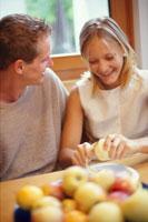 ダイニングテーブルでリンゴをむくカップル