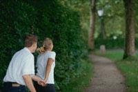 森の小道を手を繋いで歩くカップル