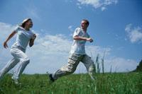 草原を走る男女