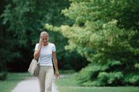 携帯で話しながら公園を歩く女性 21022002029| 写真素材・ストックフォト・画像・イラスト素材|アマナイメージズ