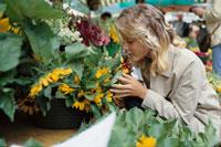 花屋でヒマワリを顔に近づける女性