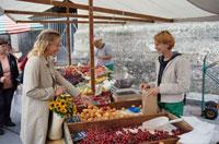 市場で果実を前に店員と話す女性