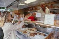 ショーウィンドゥケースからパンを渡す女性