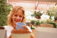 市場で青いカップを見つめる女性 21022002036| 写真素材・ストックフォト・画像・イラスト素材|アマナイメージズ