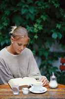 木の机で本を広げて読む女性
