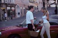 赤いオープンカーの前の外国人カップル 21022002041| 写真素材・ストックフォト・画像・イラスト素材|アマナイメージズ