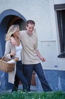 軒先で肩を組む買物帰りのカップル