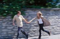 街中を女性の手を引き走るカップル 21022002045| 写真素材・ストックフォト・画像・イラスト素材|アマナイメージズ