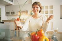 テーブルでミニトマトを持つ外国人女性