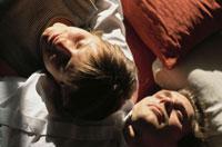ベットに寝そべる外国人男女 21022002081| 写真素材・ストックフォト・画像・イラスト素材|アマナイメージズ