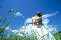 麦畑の中で空を仰ぐ白い服の女性