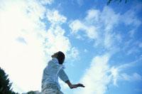 青空を仰ぐ白い服の女性