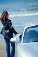 浜辺の車と傍らの女性