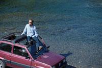 車の屋根に座る男性