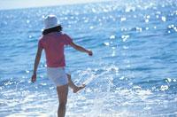 水際で水面を蹴る女性