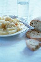 パンとお皿の上のパスタとフォーク