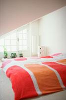 赤やピンクのベッドカバーのベッドルーム