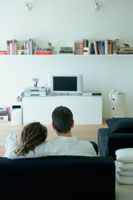 ソファに並んでテレビを見るカップル