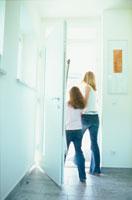 ドアから出る母と娘の後ろ姿