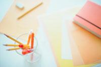 赤やオレンジ色のノートとペン類